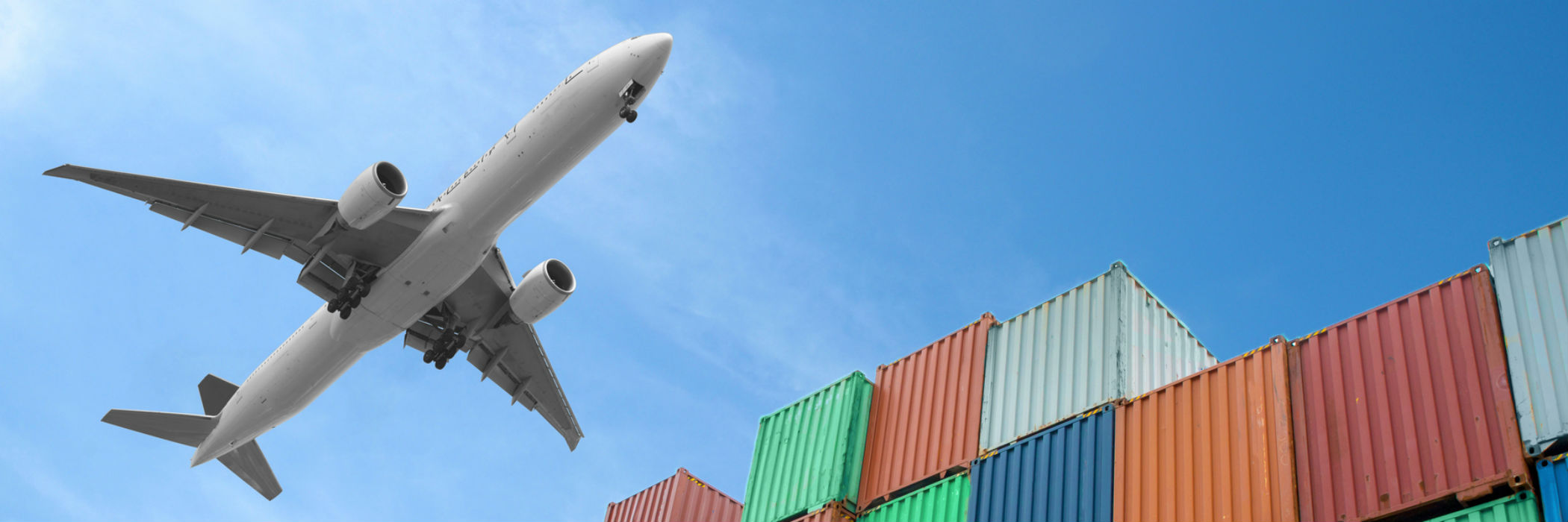 Plane flying over cargo containers