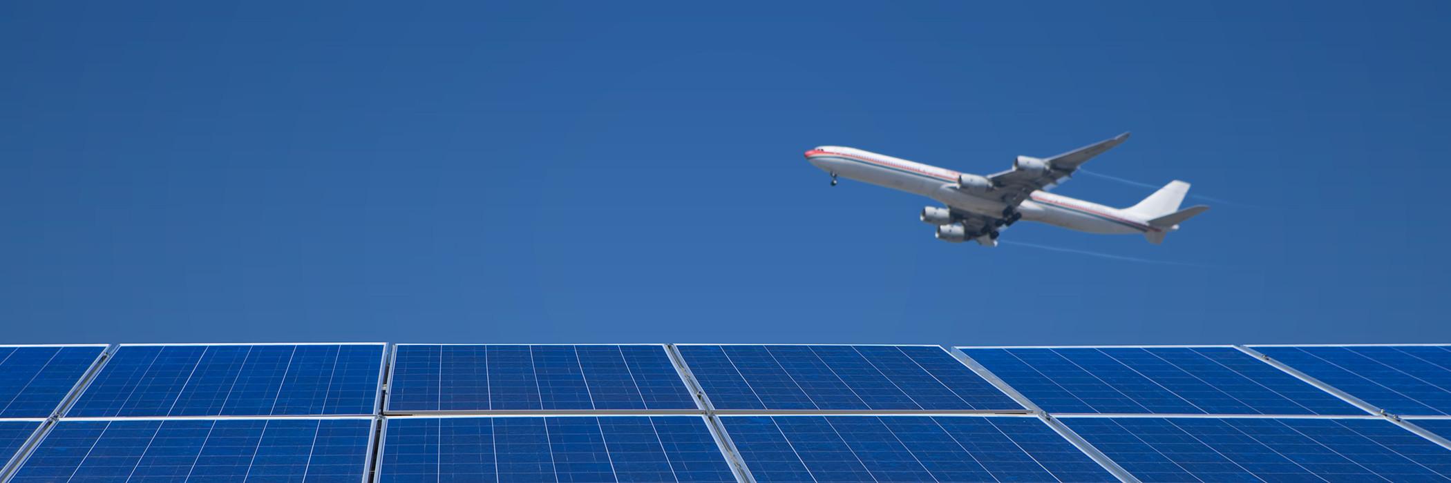 Jet flying over solar panels