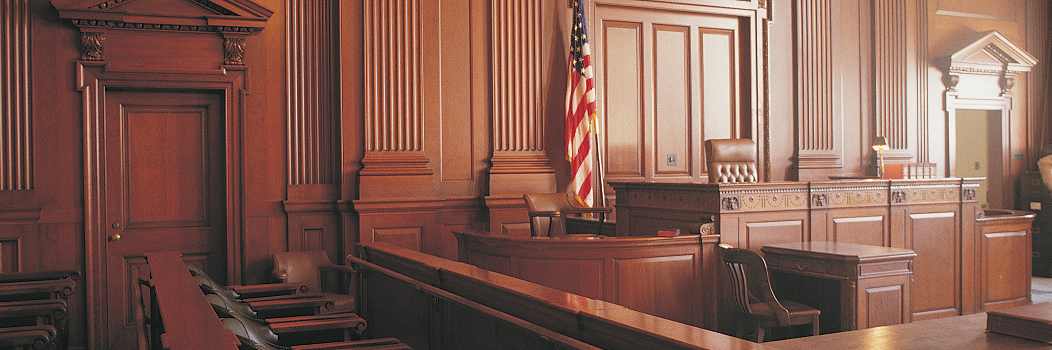 Empty wood-paneled courtroom with American flag
