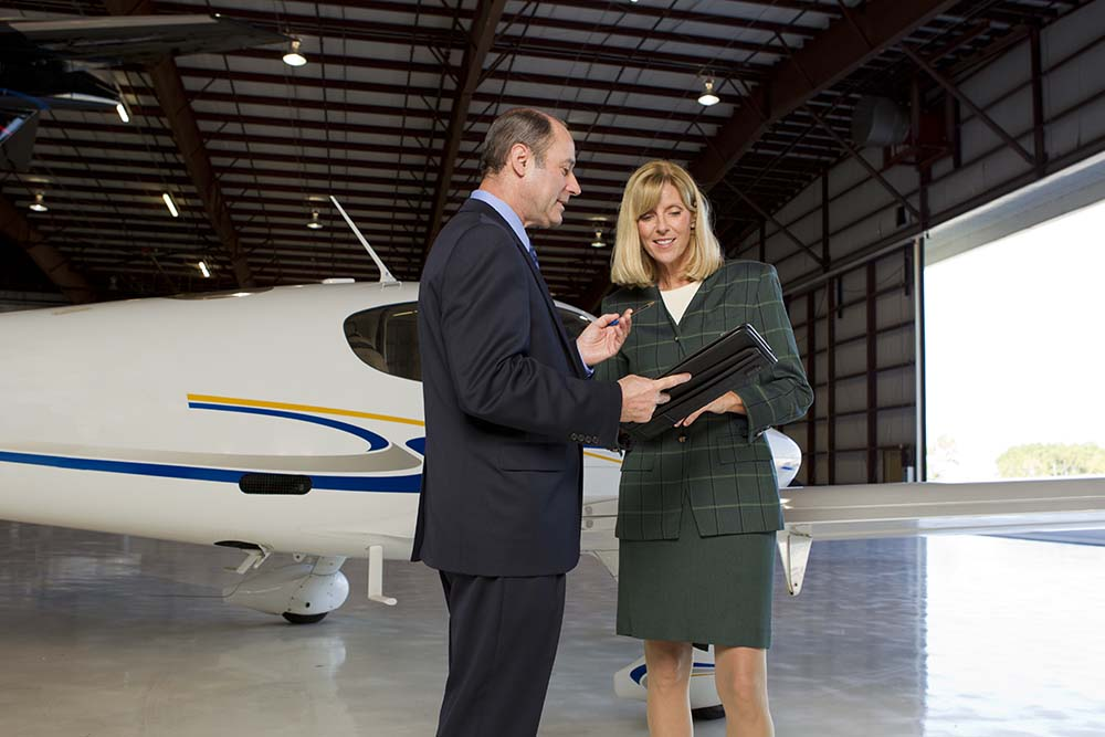 Two businesspeople consulting in front of small plane in hangar