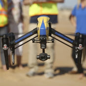 Drone hovering low over beach with operating crew in background