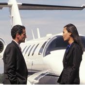 Businesspeople talking on runway in front of private jet