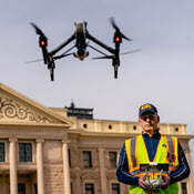 Operator flying sUAS in front of historic-looking building