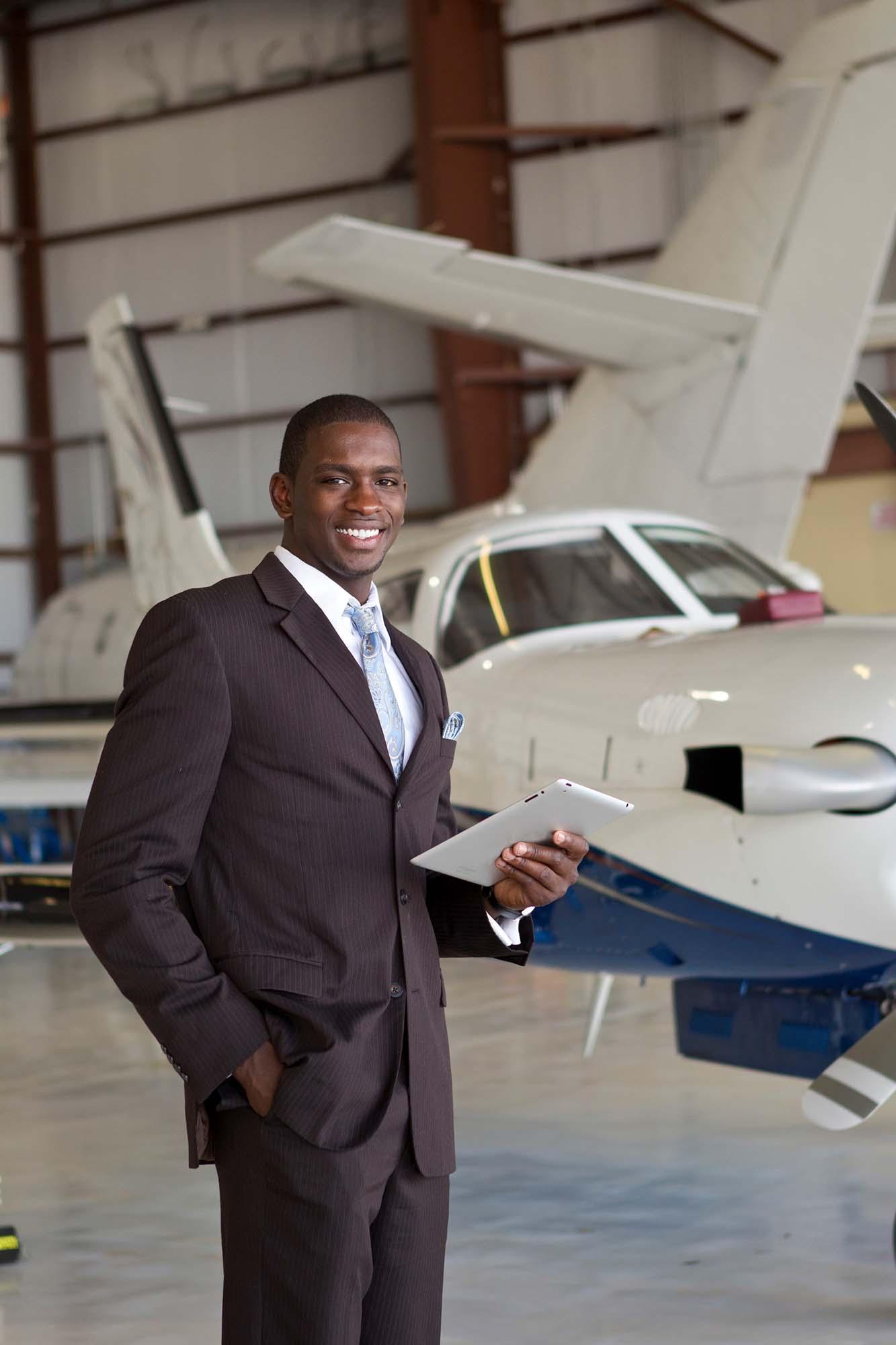 Confident businessman in airplane hangar