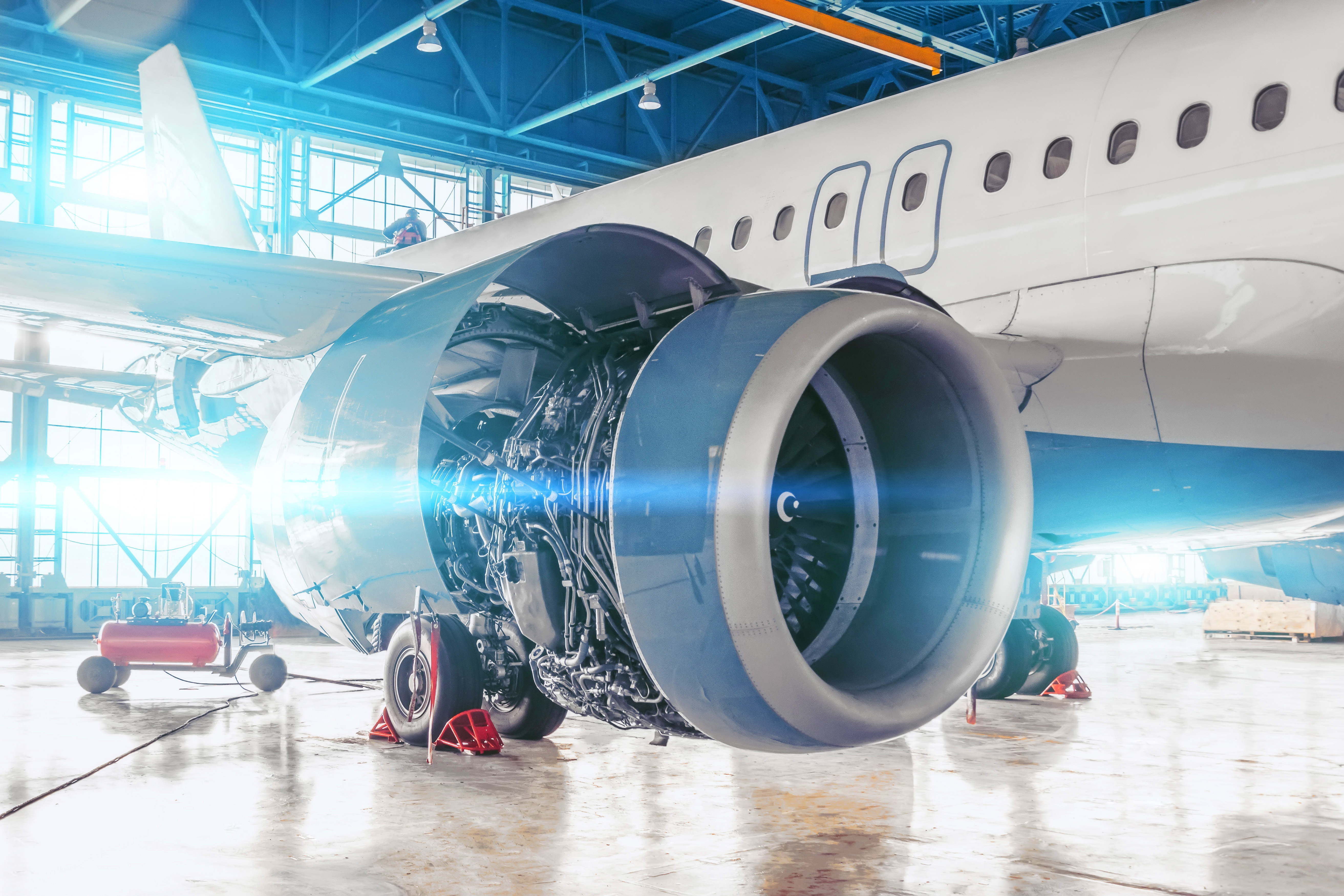 Repair and maintenance of aircraft jet engine with hood open on the wing.